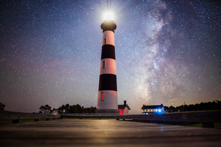 The Milky Way shines over the Bodie Island Lighthouse, reflecting off of the boardwalk.