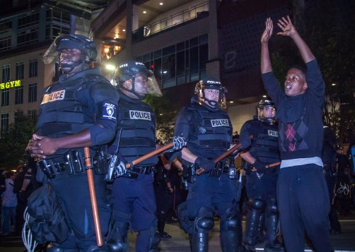 A protester walks in front of the riot squad, hands raised to signify the recent shootings. Uptown Charlotte, NC 9/21/16