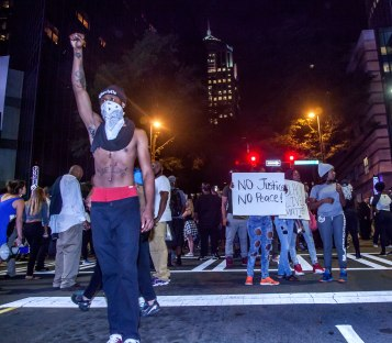 A protester stands tall with fist raised as the tension of the riot grows. Uptown Charlotte, NC 9/21/16