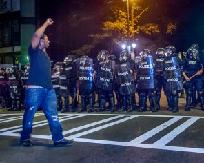 A protester silently walks with his fist in the air in front of the riot squad. Uptown Charlotte, NC 9/21/16