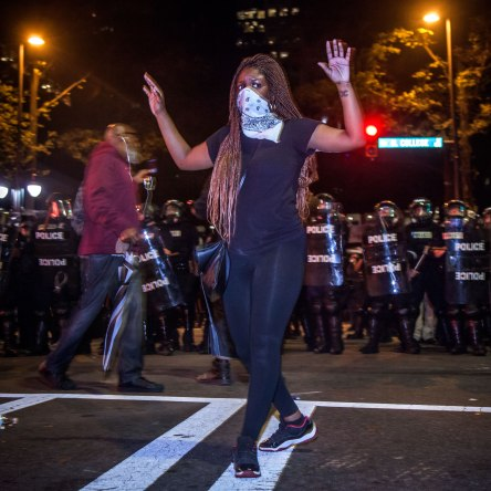"A protester silently walks with her hands in the air. ""Hands Up, Don't Shoot"" could be heard chanted by the protesters throughout the night. Uptown Charlotte, NC 9/21/16"
