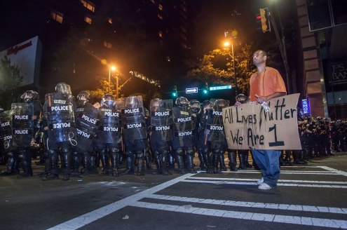 During peak rioting and chaos, a protester boldly walks in front of the riot squad with his sign. Uptown Charlotte, NC 9/21/16