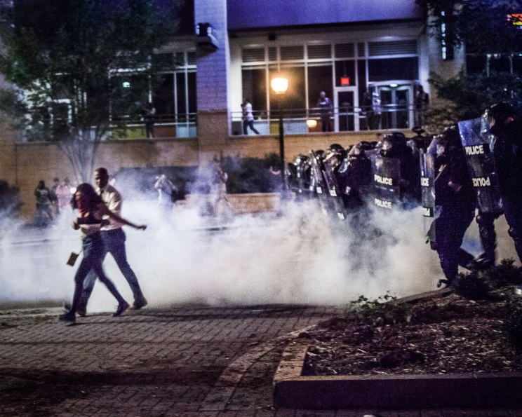 Protesters scurry away from a riot squad 'charge', meant to disperse the crowd. Tear gas was deployed in the road in front of the advancing line. Uptown Charlotte, NC 9/21/16