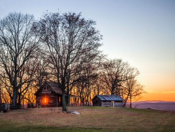 Sunstar and a couple of older cabins along a ridge north of Hanging Rock. Overlooking the Blue Ridge Mountains, at Singletree Gun & Plough. Captured March 19, 2017.