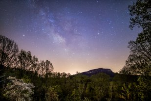 Milky Way above Moore's Knob and a dogwood in bloom, lit by the lights from the lodge at Singletree Gun and Plow