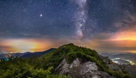 Milky Way and stars above the blueberry bushes on top of a peak in northwestern North Carolina, city lights on either side of the thin ridge.