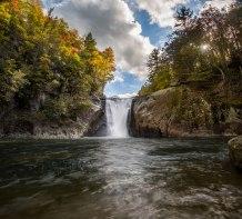 Sun rakes across autumn colored trees at Elk River Falls in western North Carolina