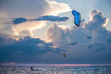 Growing storms approach kiteboarders on the Pamlico Sound just before sunset. Captured off of on the sound-side of the Outer Banks in Waves, NC. This was during the week of the international Triple-S kiteboarding competition, and lots of kiteboarders in the sound and ocean everyday.